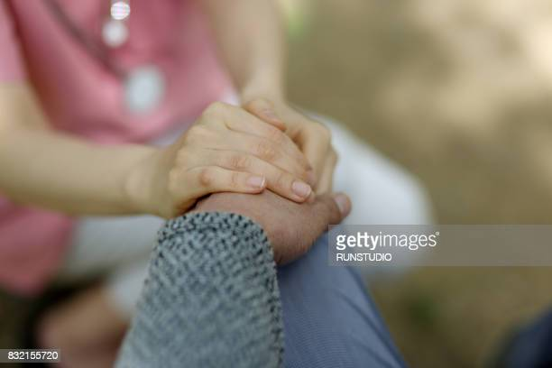 image of a nurse holding the patient's hand - assistere foto e immagini stock