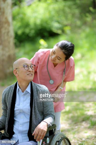 Image of a nurse walking in the park with an old man