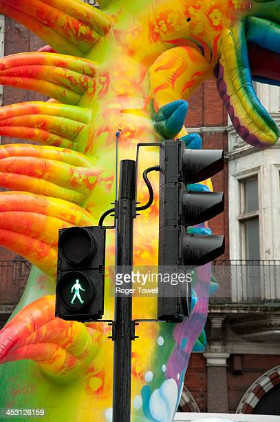 "Image of a pedestrian traffic light with grren figure illuminated and a background of an inflatable multicolour ""dragon"" which was taking part in a..."
