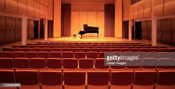 image of a piano on stage inside an empty concert hall - theatrical performance stock pictures, royalty-free photos & images
