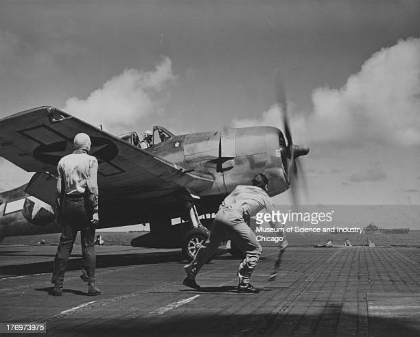 Image of a US Navy Hellcat fighter pilot getting the take off signal from the deck crew of a United States Navy aircraft carrier another ship can be...