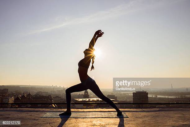 image of a woman doing yoga on a rooftop - majestoso imagens e fotografias de stock