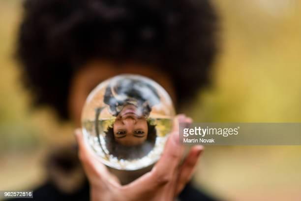 image of a woman reflecting in crystal ball - terugtrekken stockfoto's en -beelden