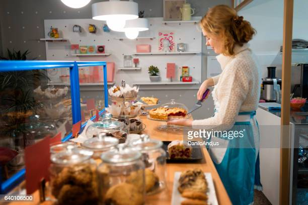 image of a young waitress arranging cakes