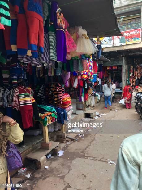 imagen del mercado callejero de agra, bazar kinari con ropa, saris / sarees, cajas desordenadas, zapatos, clientes de compras, por el fuerte de agra y jama masjid mezquita templo foto - agra jama masjid mosque fotografías e imágenes de stock