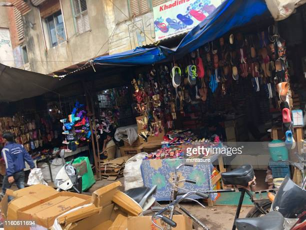image of agra street market, kinari bazaar with shoes, trainers and flip-flops, untidy boxes, customers shopping, by agra fort and jama masjid mosque temple photo - agra jama masjid mosque stock pictures, royalty-free photos & images