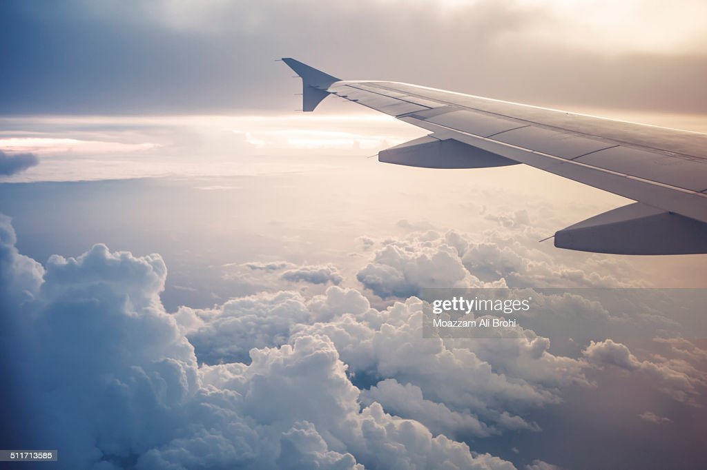 Image of airplane wing flying above the clouds : Stock Photo