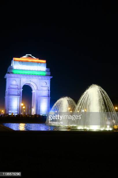 image of all india war memorial / new delhi india gate night time view with crowds of tourists, illuminated gateway arch and fountain - india gate stock pictures, royalty-free photos & images
