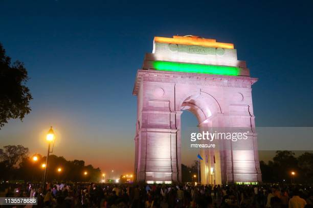 image of all india war memorial / new delhi india gate night time view with crowds of tourists, illuminated gateway arch - india gate stock pictures, royalty-free photos & images