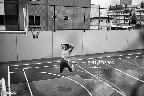 image of an athletic young man slam dunking on a rainy day - tirare la palla foto e immagini stock