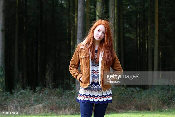 image of attractive girl, long red hair, hands in pockets - redhead girl stock photos and pictures