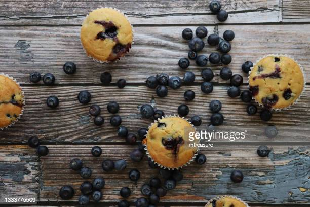 image of batch of freshly baked blueberry muffins in paper cake cases surrounded by fresh blueberries, wood grain background, elevated view - indulgence stock pictures, royalty-free photos & images