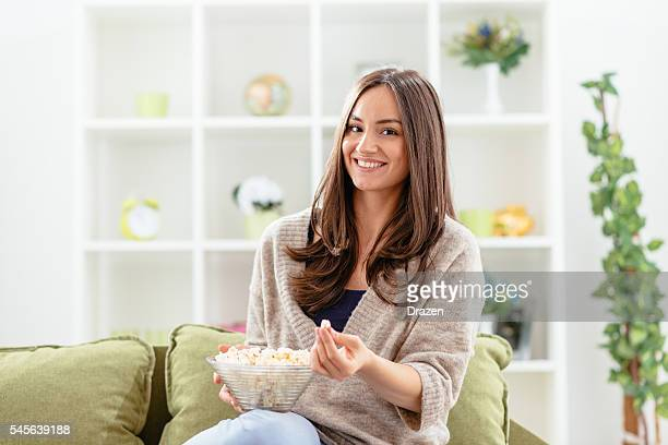 Image of beautiful woman at home, eating popcorn