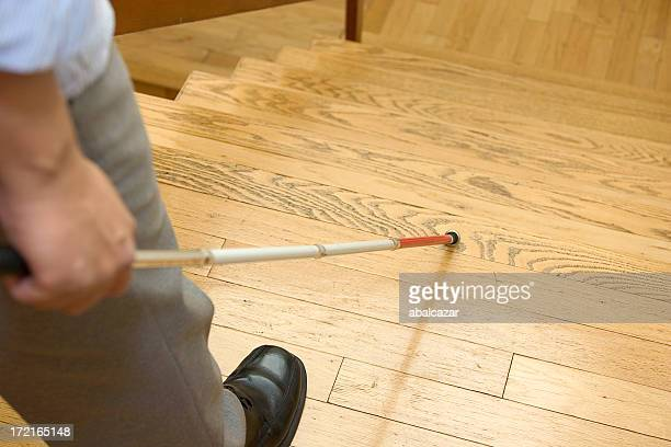 Image of blind man with walking stick about to go downstairs