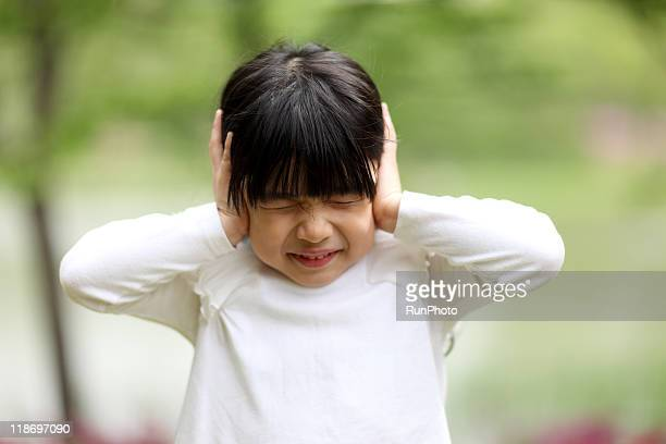 Image of child playing,girl have closed her ears