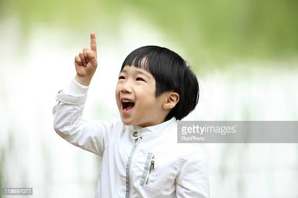 Image of child,pointing at the sky, laughing boy
