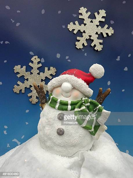 Image of Christmas snowman garden ornament with bobble-hat, snowflake background