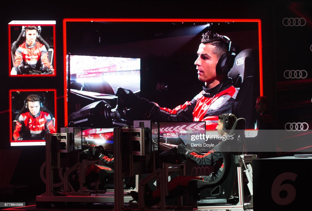 Image of Cristiano Ronaldo of Real Madrid CF seen on large screen as he races team mate Marco Asensio (R) in their simulated Formula-e cars during a race with his teammates during the Audi Handover Sponsorship deal with Real Madrid at the Ciudad Deportivo training grounds on November 23, 2017 in Madrid, Spain.