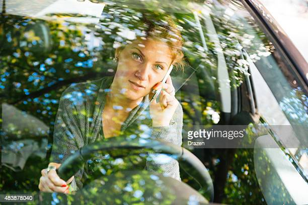 Image of driver using smartphone while driving through windshield