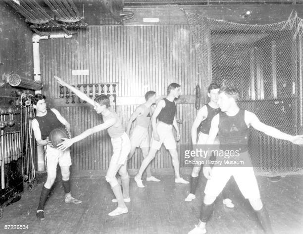 Image of Evanston YMCA basketball team, six players in a defensive play in a gymnasium in Evanston, Illinois, 1905.