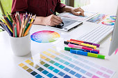 Image of female creative graphic designer working on color selection and drawing on graphics tablet at workplace