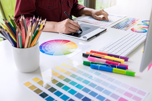Image of female creative graphic designer working on color selection and drawing on graphics tablet at workplace 1057613484