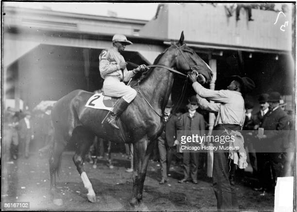 Image of Flying Torpedo being positioned for viewing in a paddock by an African American jockey and handler at Harlem Race Track located near...