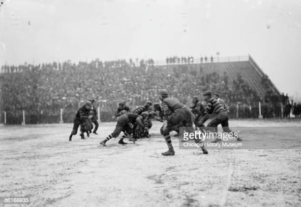 Image of football players on a snowy field beginning to run after ball was snapped during a Hyde Park High School Brooklyn football game at Marshall...