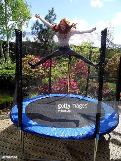 Image of girl jumping on trampoline in garden, safety net