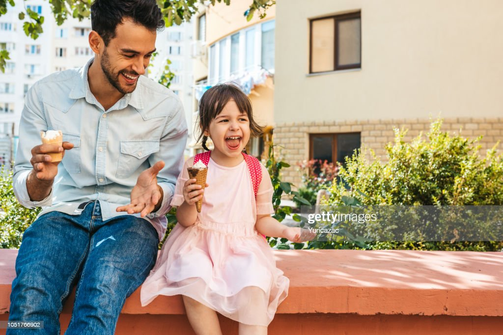 Image of happy cute little girl sitting with dad on the city street and eating ice-cream outdoor. Fun girl kid and father have fun and playing outside. Good relationship between dad and daughter : Stock Photo