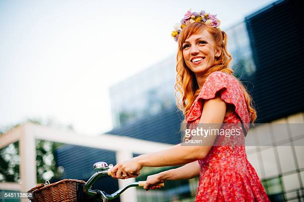 Image of happy ginger girl with hair accessory and bicycle