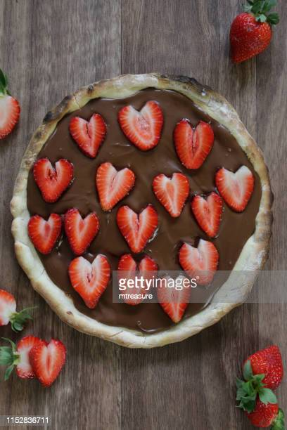 image of homemade chocolate pizza with strawberries and icing sugar, baked pizza crust filled with hazelnut chocolate spread and topped with romantic red love heart shape slices of strawberries / strawberries fruit, ready to be sliced and eaten as pudding - sweet food stock pictures, royalty-free photos & images