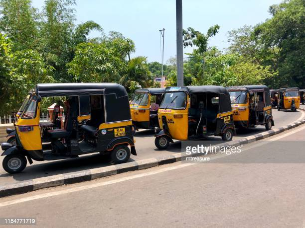 image of indian auto rickshaws taxis, yellow and black tuk tuks at kovalam railway station, cab rank in kerala, india - fare stock pictures, royalty-free photos & images