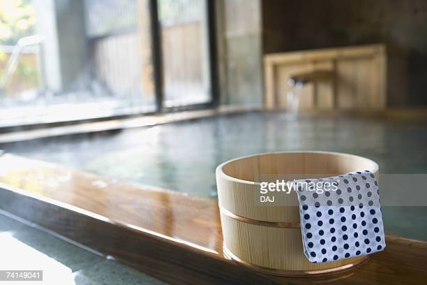 image of japanese outdoor hot spring bath, tub and tenugui at the side, close up, differential focus - 温泉 ストックフォトと画像