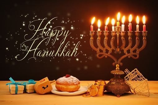 image of jewish holiday Hanukkah background with traditional spinnig top, menorah (traditional candelabra) and burning candles. 1065480886