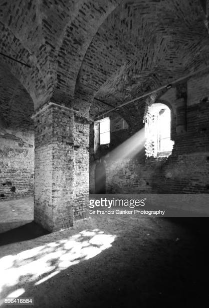 B&W image of light sunbeams through the window inside Staffarda Abbey in Revello, Piedmont, Italy