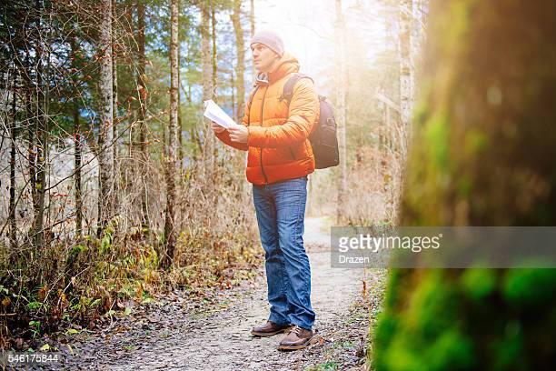 Image of man hiking and orienteering in woods in winter