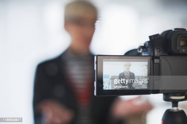 image of mature female vlogger on camera flip screen - live streaming stock pictures, royalty-free photos & images