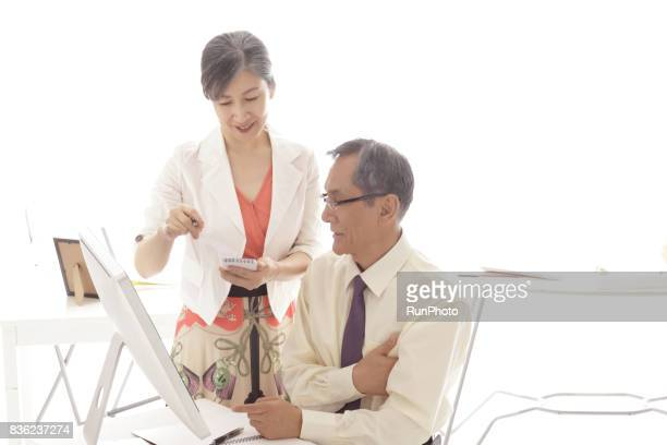 Image of middle-aged couple working in the office