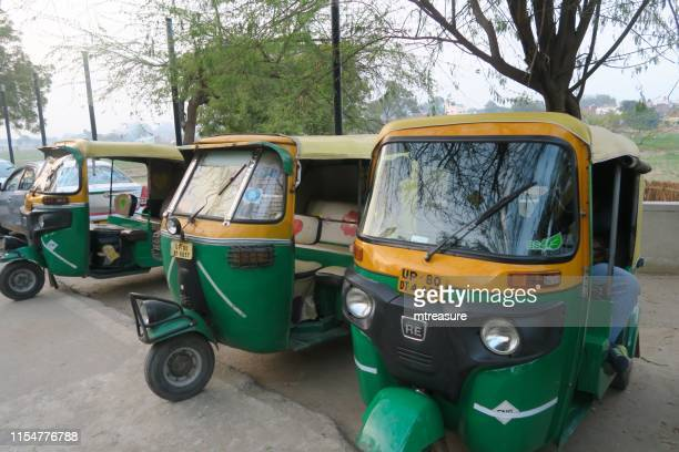 image of parked indian auto rickshaws / green and yellow tuk tuks / mini taxi cabs on streets of new delhi, uttar pradesh, india, powered by cng gas fuel, waiting for passengers fares - auto rickshaw stock pictures, royalty-free photos & images