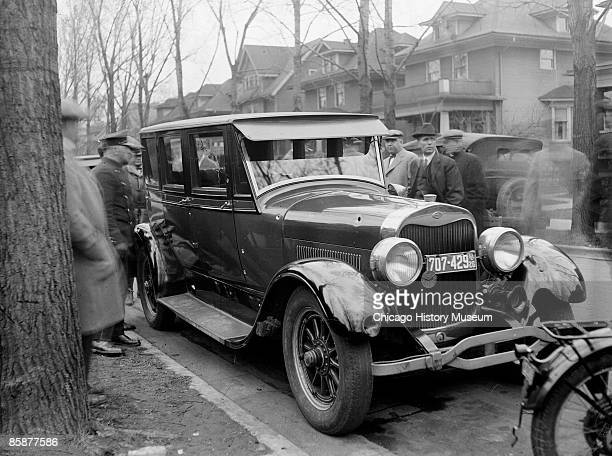 Image of policemen and civilians standing in the street in Chicago Illinois and looking at the Lincoln automobile in which attorney William H...