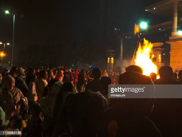 image of punjab lohri festival holiday crowds in new delhi, india, with indians dancing around bonfire flames - makar sankranti stock pictures, royalty-free photos & images