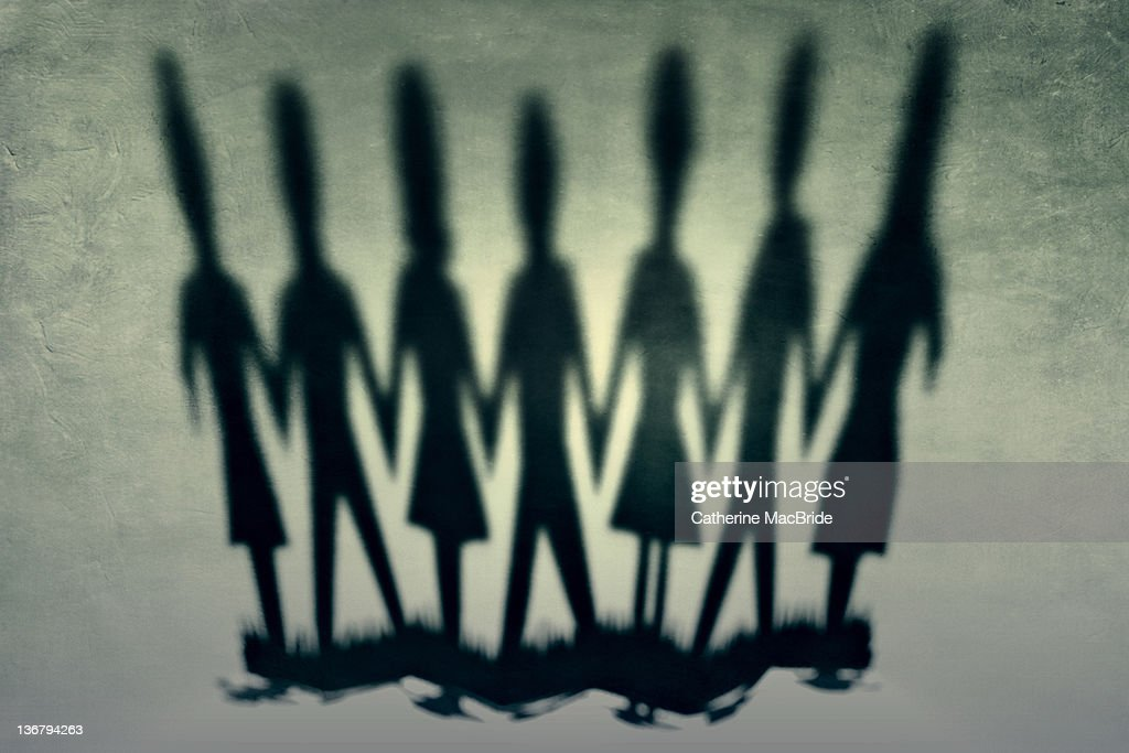 Image of shadows cast from chain of paper people : Stock Photo