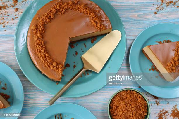 image of sliced toffee caramel cheesecake, buttery biscuit base, fluffy mascarpone cream cheese topping covered with toffee caramel sauce, decorated with biscuit crumbs, turquoise blue plates, gold cutlery, blue wood grain background, elevated view - caramelo de manteiga comida doce imagens e fotografias de stock