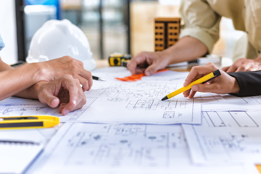 Image of team engineer checks construction blueprints on new project with engineering tools at desk in office. 929029342