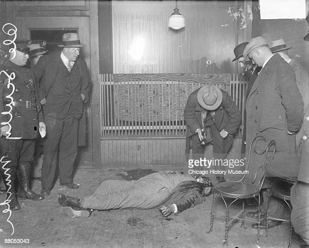 Image of the corpse of murder victim Ole Scully lying on the floor in a room in Chicago, Illinois, 1928. A policeman wearing a suit is leaning over...