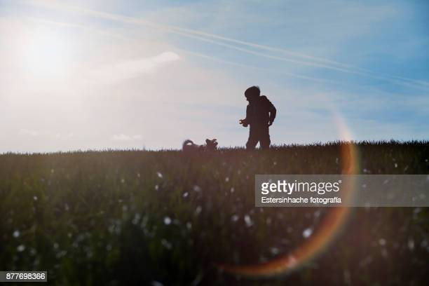 Image of the silhouette of a boy and a dog in front of a cloudy sky