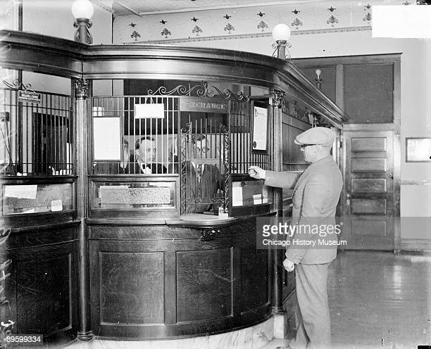 Image of three unidentified men reenacting a robbery at the Lemont National Bank in Lemont, Illinois, 1929. One man is holding up his hand to...