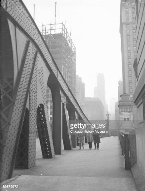 Image of three unidentified men walking toward the camera on the newly opened LaSalle Street Bridge which spanned the Chicago River from the Loop to...