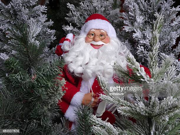 image of toy santa claus figure with fake christmas trees - cartoon santa claus stock photos and pictures